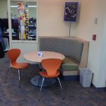 reading area with orange chairs & padded bench